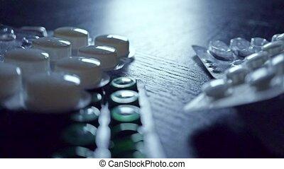 Drug blister packs fall on dark table. 2 slow motion shots...