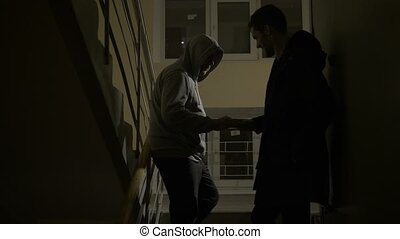 Drug dealer selling drugs to addict on staircase - Drug...