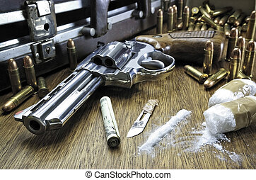 Image concept of drug trafficking. Gun, U.S. dollars, bullets and cocaine on the table.