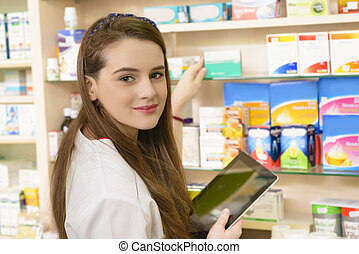 Drugstore - Young female pharmacist in a drugstore working...
