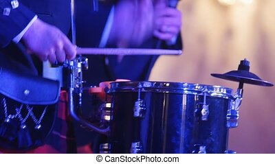 Drum performer plays drumstick at the stage