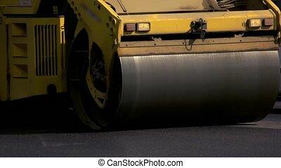Drum roller on road. Dark asphalt surface. Tight schedule of...