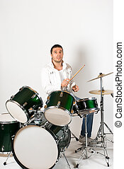 Drummer - Active drummer playing at drums set in a studio
