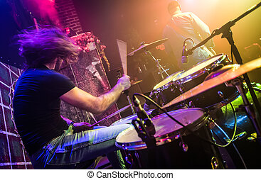 Drummer (blurred motion) playing on drum set on stage. Focus...