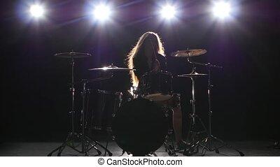 Drummer comes off at a rock concert. Black smoke background....