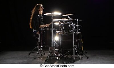 Drummer girl starts playing energetic music, she smiles. Black background