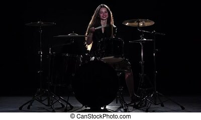 Drummer girl starts playing energetic music, she smiles. Black background. Slow motion