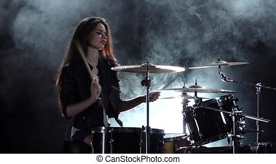 Drummer in a leather jacket plays energetic music. Black smoke background. Side view. Slow motion