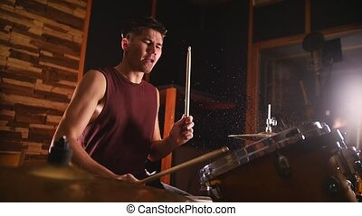 Drummer passionately plays music on wet drums in studio in a garage.