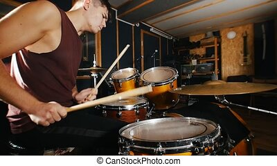 Drummer passionately plays music on wet drums in studio