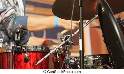 Drummer playing drums with drum sticks, close-up low angle view