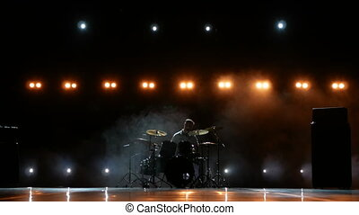 Drummer playing drums with smoke and powder on the background
