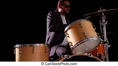 Drummer playing his drum kit on black background