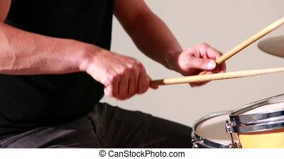 Drummer playing his drum kit on white background