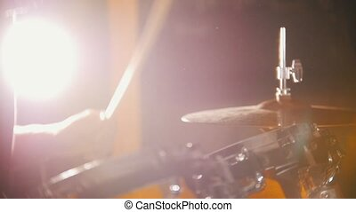 Drummer playing in studio. Drumsticks, bright light