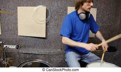 drummer playing on dums in recording studio, moving camera