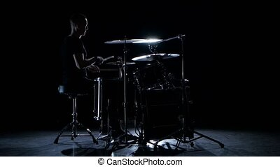 Drummer plays energetic music on the drum. Black background. Side view