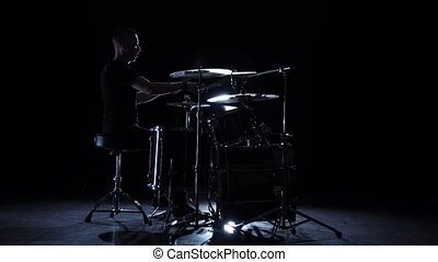 Drummer plays energetic music on the drum. Black background. Side view. Slow motion
