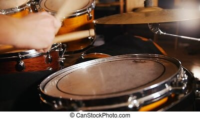 Drummer plays music on wet drums in studio. Drums close up