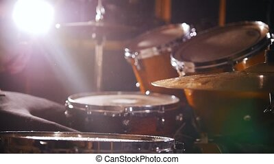 Drummer plays music on wet drums in studio in a garage. Close up