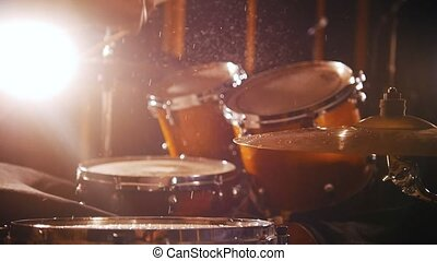 Drummer plays music on wet drums in studio in a garage.