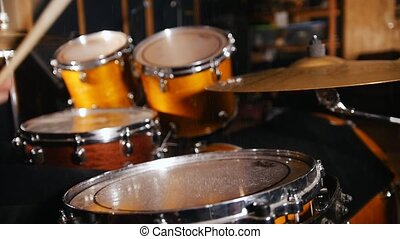 Drummer plays music on wet drums in studio