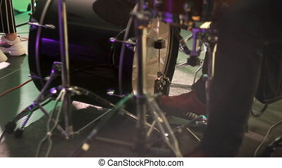 Drummer plays the drum by kicking the pedal. The drummer's foot moves the drum bass pedal.