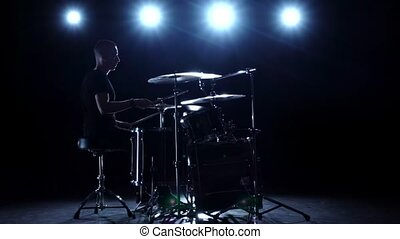 Drummer plays the melody on the drums energetically. Black background. Back light. Silhouette. Slow motion