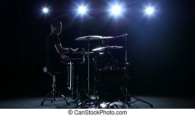 Drummer plays the melody on the drums energetically. Black background. Back light. Silhouette
