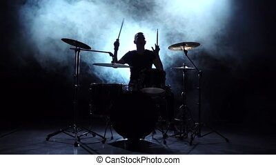 Drummer plays the melody on the drums energetically. Black background. Silhouette. Slow motion