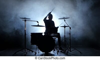 Drummer plays the melody on the drums energetically. Black background. Silhouette