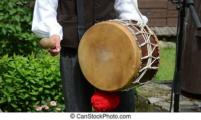 Drummer play folk music with drum and stick in rural village party.