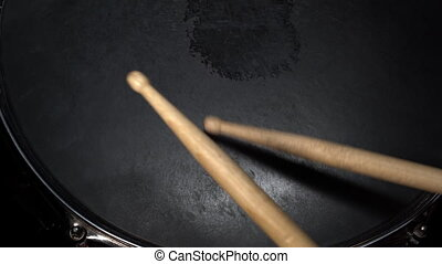 Drumsticks hits on the snare drum. View from above. Drummer plays active rhytm