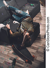 Drunk bearded young man sleeping on couch in messy room after party