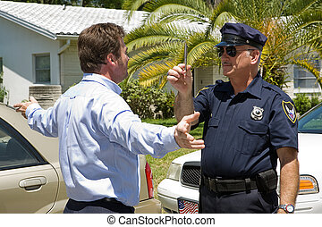 Police officer giving a sobriety test to a drunk driver.