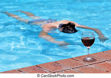 Drunk drowning person - A cup of red wine on a pool side ...