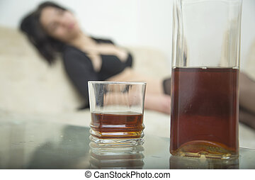 Drunk girl on sofa front of glasses and bottles whiskey