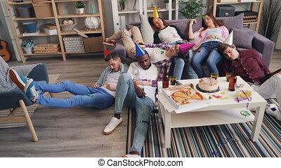 Drunk girls and guys sleeping on floor and sofa after joyful...