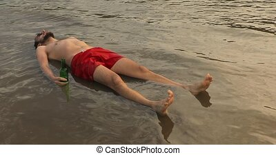Drunk guy lying in shallow water - Young man lying on back ...