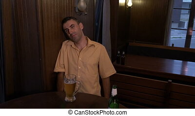 Drunk guy sitting a table in a pub cannot hold his glass with beer
