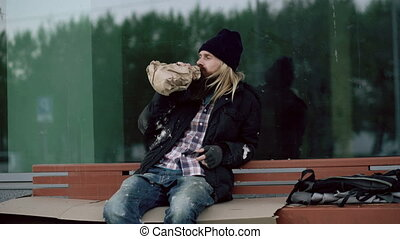 Drunk homeless young man talking to people walking near him and drink alcohol sitting on bench at the sidewalk