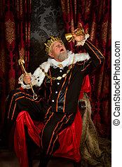 Old funny king getting drunk holding a golden goblet