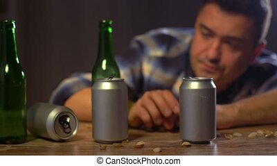 alcoholism, alcohol addiction and people concept - male alcoholic drinking beer from bottles and cans at home