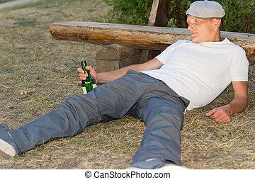 Drunk man fallen down on the ground in the park - Drunk man...