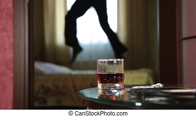 drunk man funny jumping on a bed. close-up glass of brandy