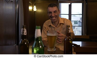 Drunk man laughing and drinking beer alone at a pub