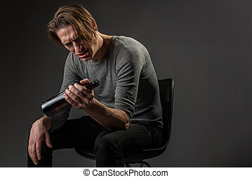 Depressed alcoholic sitting in chair with bottle of beer. Copy space in right side. Isolated on background