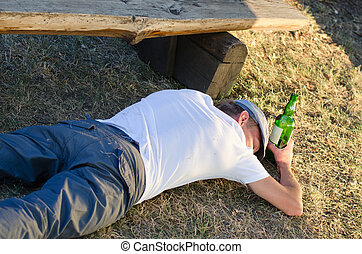 Drunk man sleeping on the ground in summer