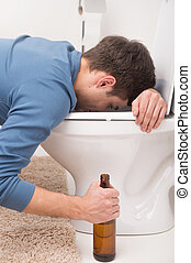 Drunk man sleeping on toilet and holding bottle. sick man is vomiting and feeling bad