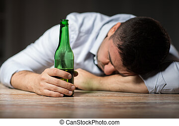 drunk man with beer bottle lying on table at night
